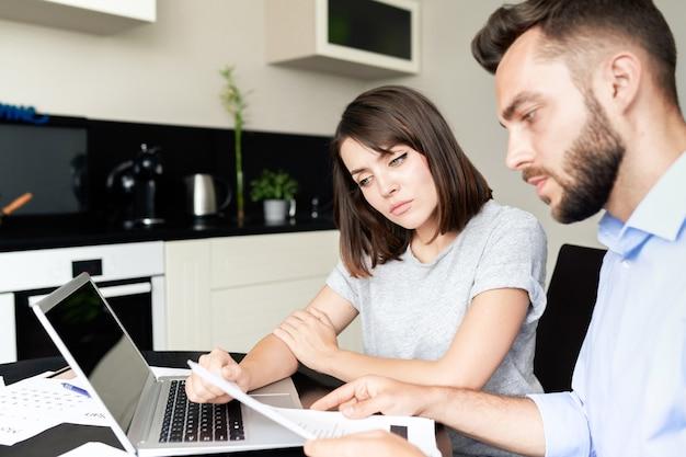 Poważna młoda para siedzi przy stole i analizuje dokumenty podczas wspólnej analizy finansów rodziny w kuchni