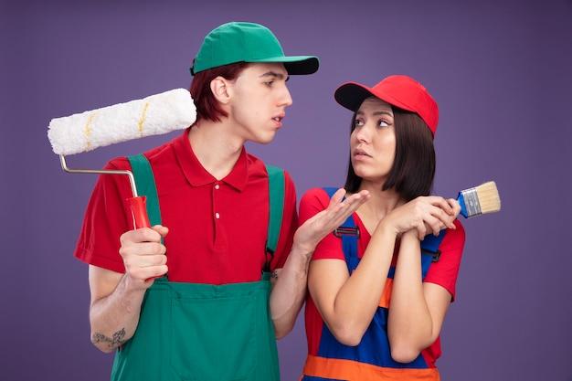 Poważna młoda para w mundurze pracownika budowlanego i czapce patrząc na siebie faceta trzymającego wałek do malowania pokazujący pustą rękę dziewczyny trzymającej pędzel obiema rękami odizolowanymi na fioletowej ścianie