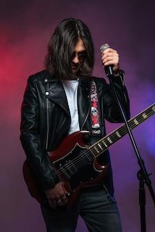Poważna młoda piosenkarka w okularach przeciwsłonecznych z długimi włosami, stojąca z mikrofonem i gitarą elektryczną na kolorowym zadymionym tle