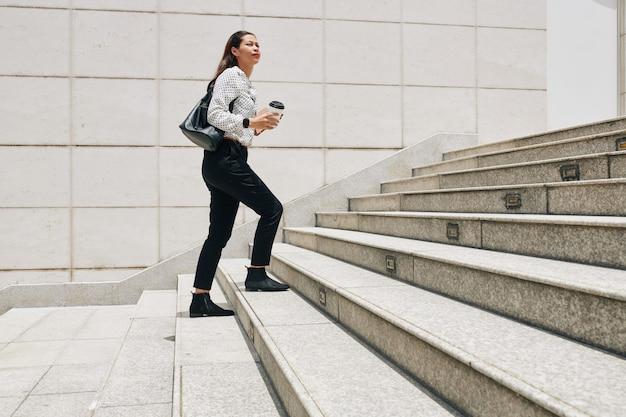 Poważna młoda przedsiębiorczyni z kawą na wynos, idąca po schodach, spiesząc się rano do pracy