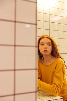 Poważna młoda rudzielec kędzierzawa dama siedzi w kawiarni