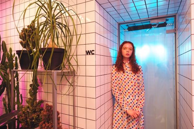 Poważna młoda rudzielec kędzierzawa dama stoi w kawiarni blisko latryny