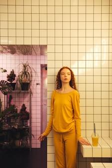 Poważna młoda rudzielec kędzierzawa dama stoi w kawiarni