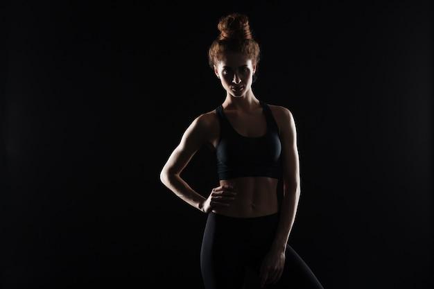 Poważna młoda sport dama stoi nad czerni ścianą