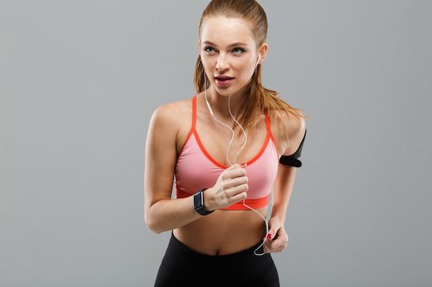 Poważna młoda sport kobieta biega odosobnioną słuchającą muzykę