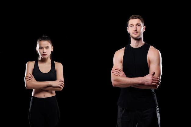 Poważna młoda sportowa para w odzieży sportowej krzyżująca ramiona przy klatce piersiowej na stojąco
