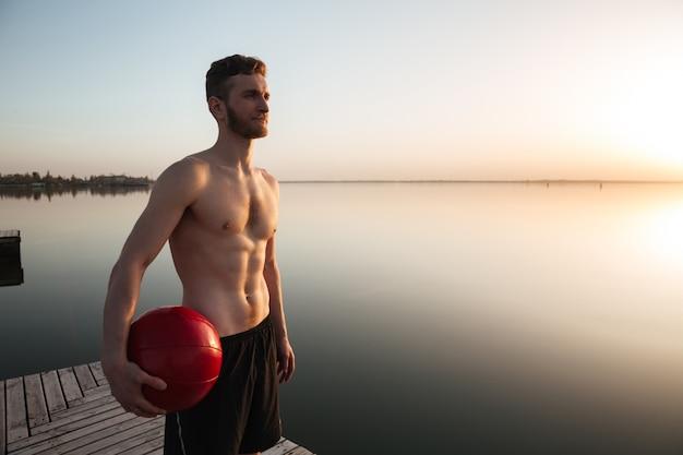 Poważna młoda sportowiec pozycja z piłką przy plażą.