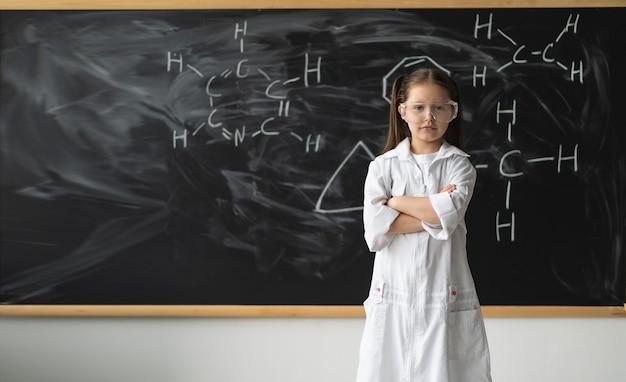 Poważna młoda studentka nauk ścisłych w okularach w fartuchu laboratoryjnym z odręcznymi rysunkami formuła naukowa powrót ...