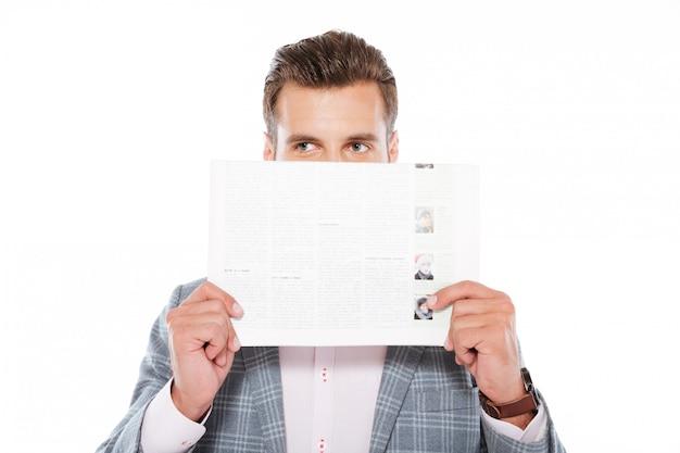 Poważna młody człowiek pozycja trzyma odosobnionego gazette