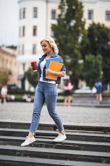 Poważna modelka blondynka idzie na zajęcia robocze przez centrum miasta, trzymając w rękach komputer z notebookami do kawy rano