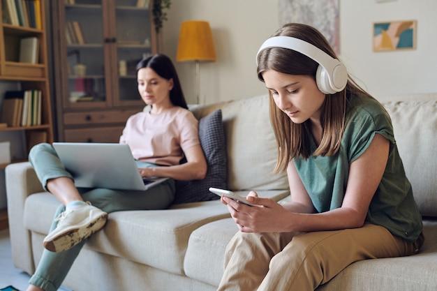 Poważna nastolatka wybiera piosenkę przez aplikację na smartfona i słucha muzyki w słuchawkach, podczas gdy jej matka pracuje z laptopem