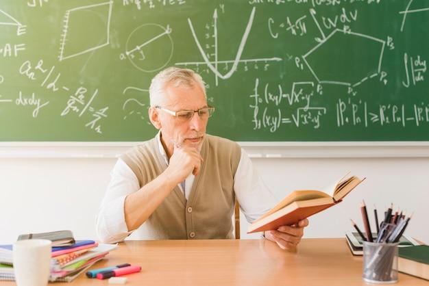 Poważna nauczyciel czytanie książki