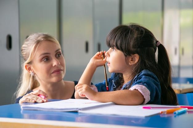 Poważna nauczycielka omawia zadanie z małym uczniem