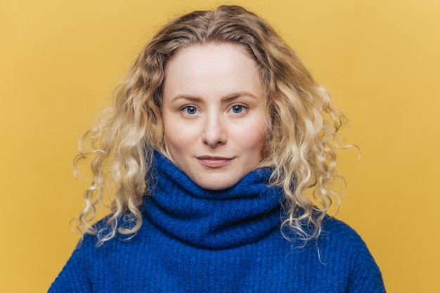 Poważna niebieskooka kobieta nosi niebieski ciepły sweter