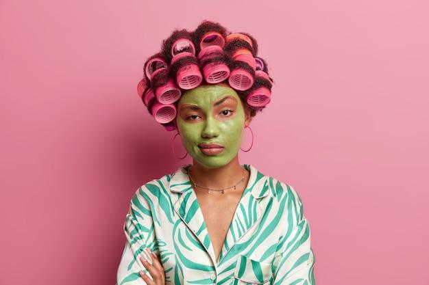Poważna, niewzruszona kobieta stoi ze skrzyżowanymi dłońmi na ciele, nudzi się podczas zabiegów kosmetycznych, nosi wałki do włosów, aby stworzyć idealne loki, zieloną maskę odmładzającą i redukującą zmarszczki
