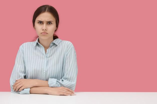 Poważna niezadowolona studentka w koszuli w paski, trzymając łokcie na biurku, marszcząca brwi, zła na niesprawiedliwą złą ocenę wystawioną przez surowego nauczyciela. na białym tle portret przed różową ścianą