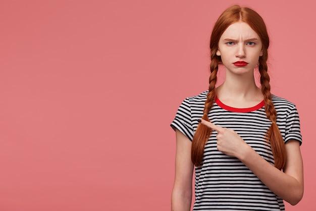 Poważna niezadowolona zła dziewczyna z dwoma rudymi warkoczykami czerwona warga, ubrana w t-shirt w paski, wskazująca palcem wskazującym w lewym górnym rogu w pustej przestrzeni kopii na białym tle