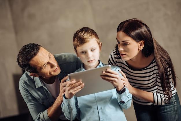 Poważna obawa. kochający młodzi rodzice stoją obok swojego nastoletniego syna i delikatnie przekonują go, aby przestał grać na tablecie, podczas gdy chłopiec nie zwracał na nich uwagi