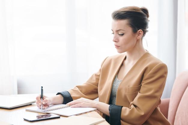 Poważna, odnosząca sukcesy przedsiębiorczyni w stylowej kurtce, siedząca przy stole w kawiarni i zapisująca zadania podczas planowania dnia