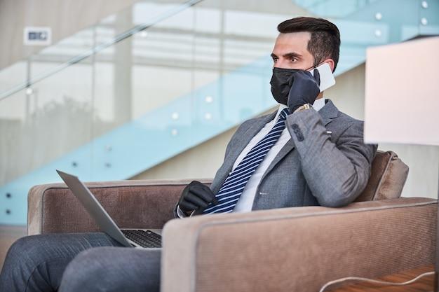 Poważna osoba rozmawiająca przez telefon siedząc z laptopem