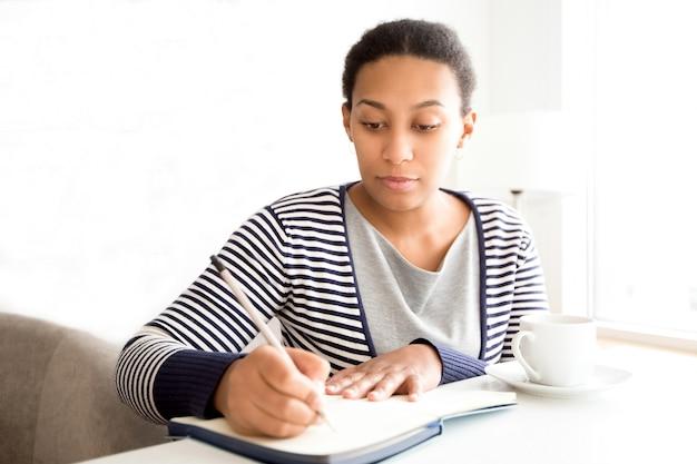 Poważna pani biznesu robienie notatek w organizatorze