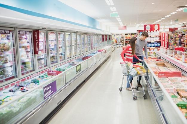 Poważna para robi sklepowi spożywczemu robić zakupy wpólnie