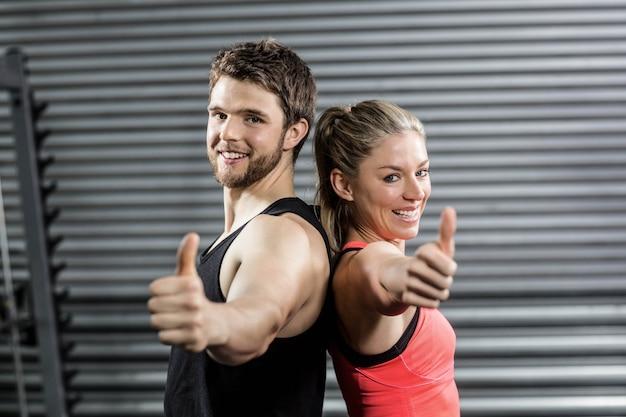Poważna para stojąca plecami do siebie na siłowni crossfit
