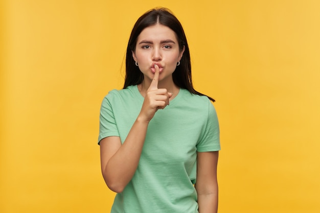 Poważna piękna brunetka młoda kobieta w miętowej koszulce wygląda surowo i pokazuje znak ciszy na białym tle nad żółtą ścianą
