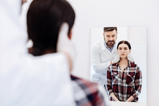 Poważna piękna miła kobieta stojąca ze swoim chirurgiem plastycznym i patrząc na swoje odbicie podczas przygotowań do operacji plastycznej