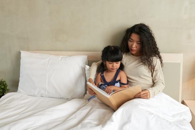 Poważna piękna młoda azjatka siedzi pod kołdrą i czyta książkę słodkiej córce w łóżku