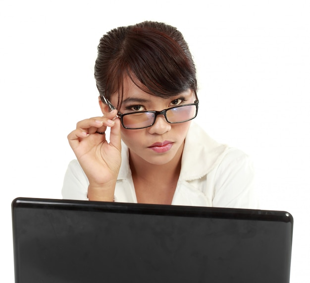 Poważna piękna młoda kobieta pracuje z jej laptopem