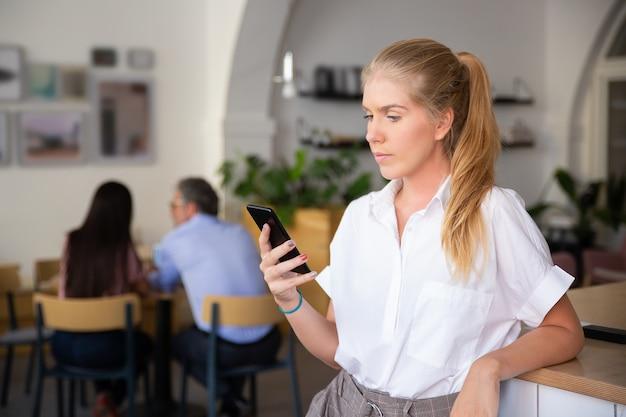 Poważna piękna młoda kobieta ubrana w białą koszulę, za pomocą smartfona, wpisując wiadomość, stojąc w przestrzeni coworkingowej