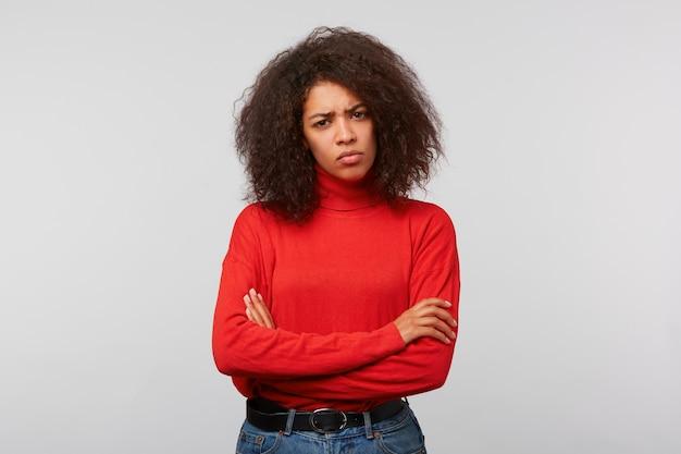 Poważna, podejrzliwa kobieta z kręconymi włosami w stylu afro, stojąca ze skrzyżowanymi rękami i marszcząca brwi