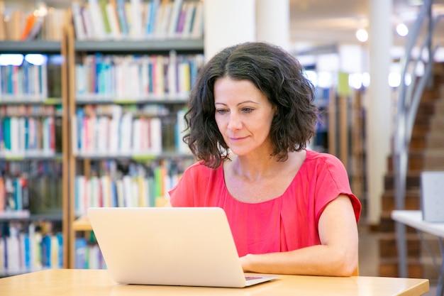 Poważna podekscytowana kobieta pracująca na komputerze