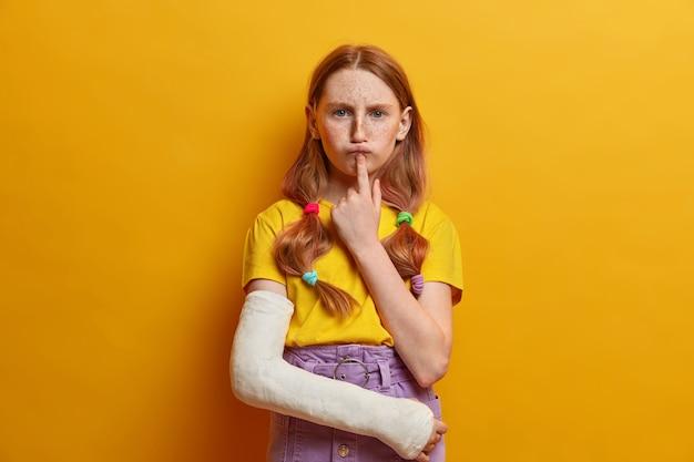 Poważna ponura dziewczyna trzyma palec wskazujący pod dolną wargą, ma poważny niezadowolony wyraz twarzy, piegowatą cerę, ubrana w letni strój, głęboko się nad czymś myśli, po upadku złamała rękę