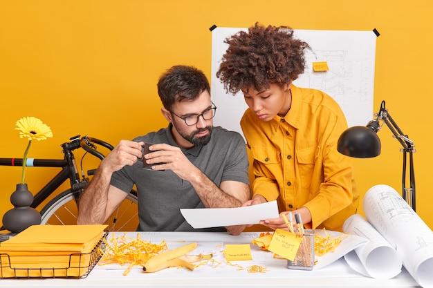 Poważna praktykantka pokazuje papier pracodawcy, przedstawia swoje pomysły na przyszły projekt pozuje przy biurku z naklejkami z naklejkami na żółtą ścianę. różnorodni studenci współpracują ze sobą