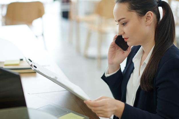 Poważna przedsiębiorczyni rozmawia przez telefon z pracownikiem, aby wyjaśnić szczegóły podczas czytania raportu