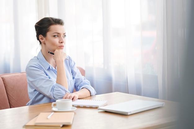 Poważna, przemyślana młoda menedżerka w niebieskiej koszuli siedzi przy stole w przytulnej kawiarni i wygląda przez okno, czekając na partnera biznesowego