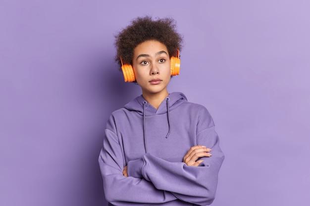 Poważna, rozważna afroamerykanka trzyma ręce skrzyżowane, słucha muzyki, myśli o czymś, co nosi zwykłą bluzę.