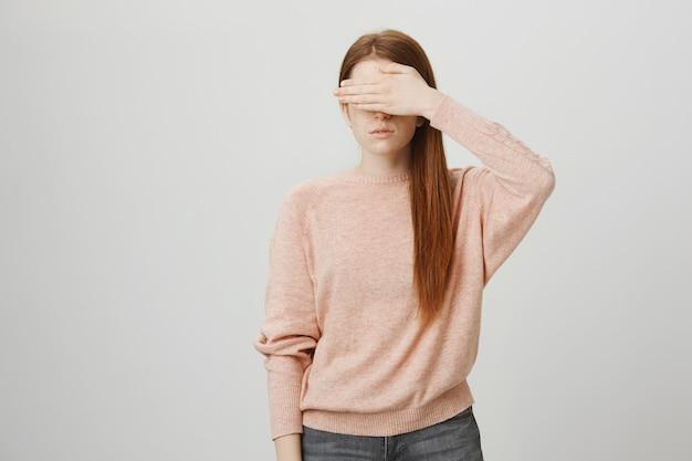 Poważna ruda dziewczyna zakrywa oczy ręką