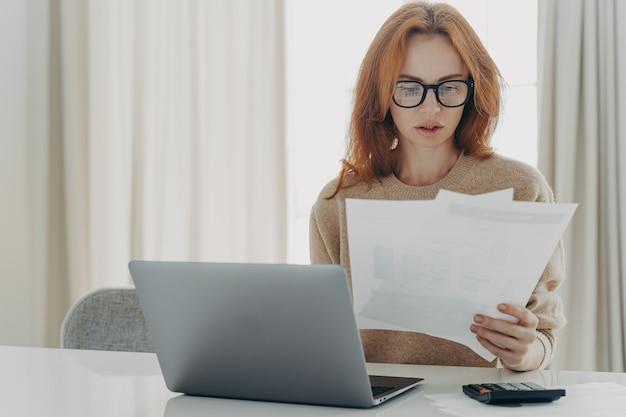 Poważna ruda kaukaska kobieta oblicza rachunki, trzyma papierowe dokumenty, skupia się na wyglądzie