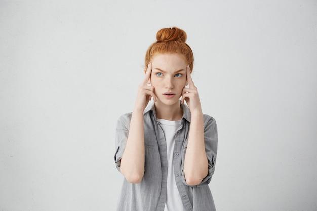 Poważna ruda młoda kobieta rasy białej trzymająca palce na skroniach i spoglądająca w bok ze skoncentrowanym i skupionym wyrazem twarzy, jakby próbowała przypomnieć sobie coś ważnego
