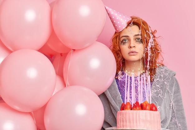 Poważna rudowłosa kobieta z wyciekającym makijażem patrzy prosto z przodu, nosi imprezowy kapelusz w kształcie stożka, szlafrok trzyma pyszne ciasto truskawkowe i nadmuchane balony pozuje na różowej ścianie