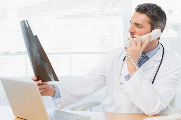 Poważna samiec lekarka egzamininuje promieniowanie rentgenowskie podczas gdy na wezwaniu