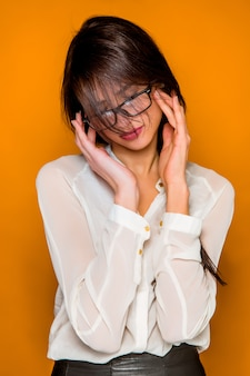 Poważna sfrustrowana młoda piękna biznesowa kobieta na pomarańcze ścianie