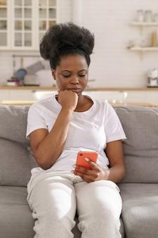 Poważna skoncentrowana czarna kobieta czyta wiadomość na smartfonie zamyślona dziewczyna dostaje złe wieści w aplikacji na telefon komórkowy