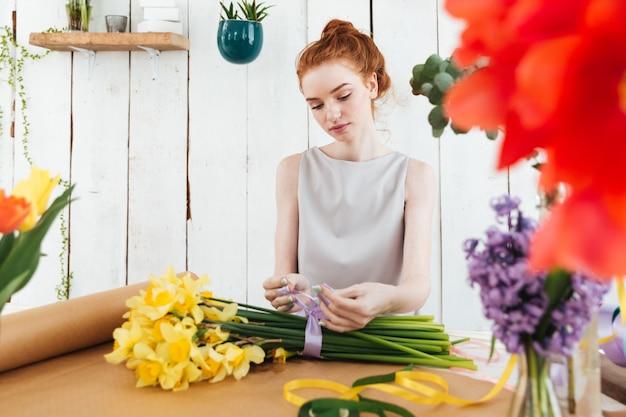 Poważna skoncentrowana kobieta robi bukietowi z faborkiem w warsztacie