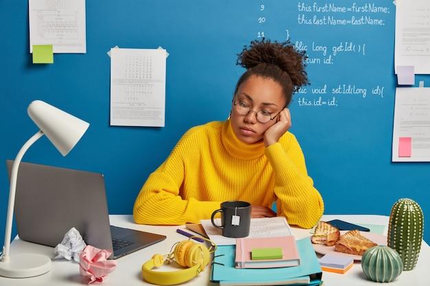 Poważna, skoncentrowana studentka korzysta z usługi edukacji online, ogląda webinarium lub kurs na laptopie, ma wiele rzeczy na stole, pije herbatę