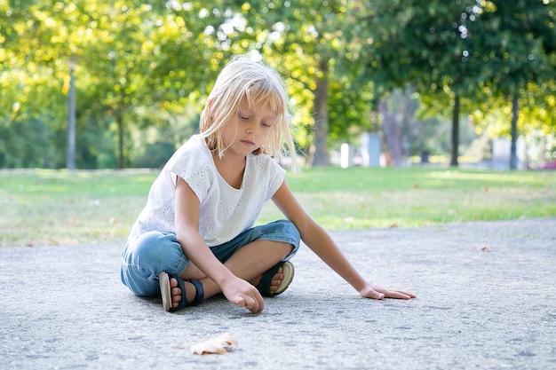 Poważna słodka jasnowłosa dziewczyna siedzi i rysuje kolorowymi kawałkami kredy. skopiuj miejsce. koncepcja dzieciństwa i kreatywności