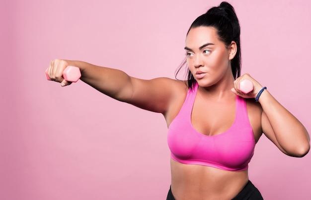 Poważna sprawa. skoncentrowana pulchna mulat kobieta robi ćwiczenia bokserskie przy użyciu małych hantli na białym tle